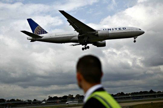 A United plane prepares to land as a ground crew member looks on at London Heathrow airport in London on Oct. 7, 2016.