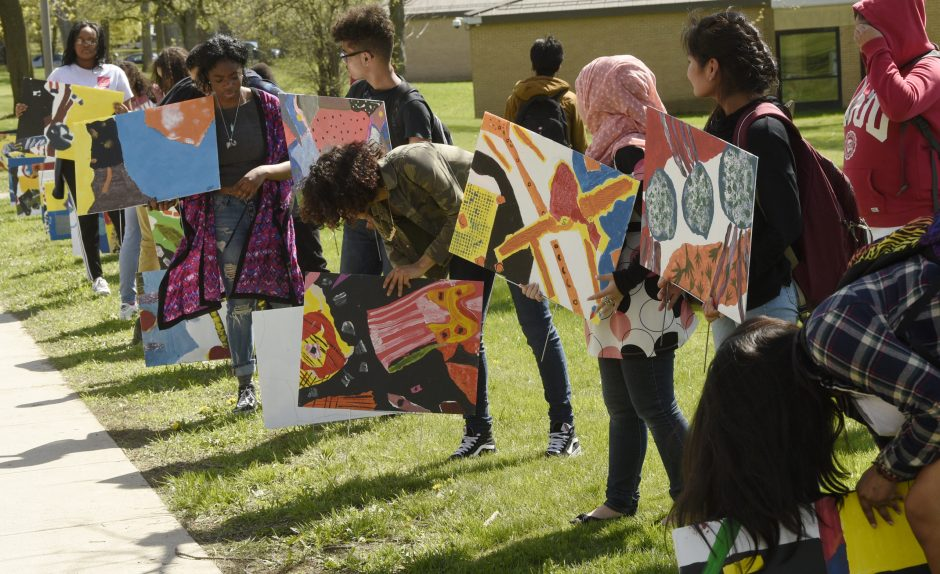 Schenectady High School students arrange artwork Friday on McClellan Street.