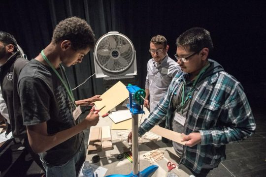 Schenectady students, under the guidance of GE Power's Jake Dotts, make parts for a paper wind turbine.