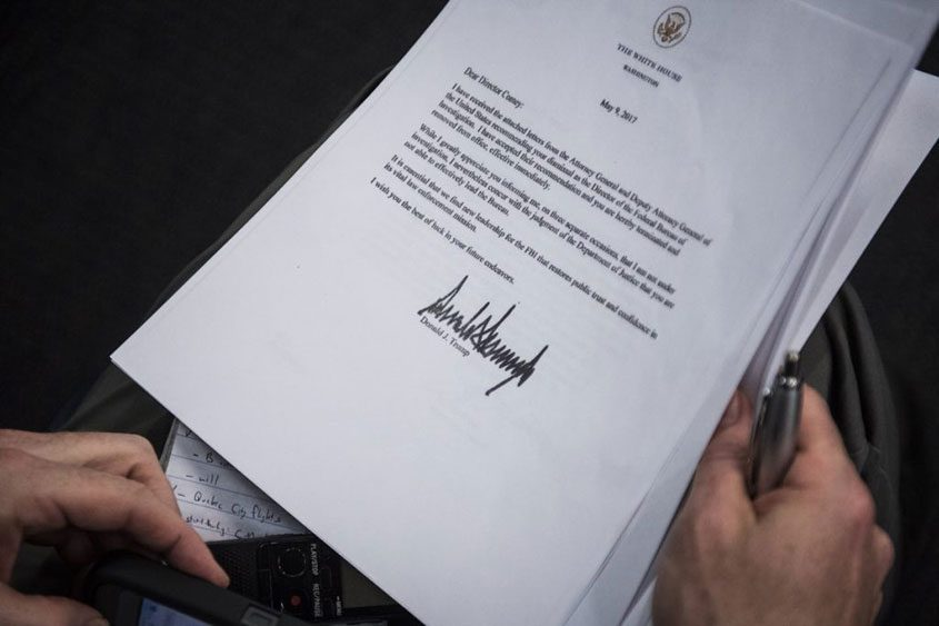 A reporter reads the letter from President Trump firing FBI Director James Comey.