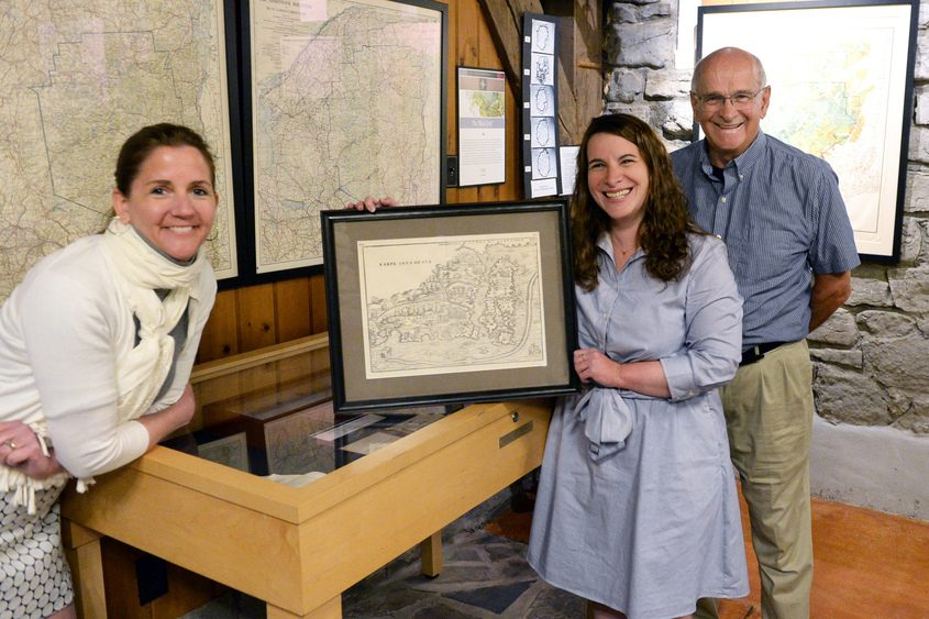 Project curators (from left) Margie Amodeo, Caroline Welsh and Cal Welsh with a 1556 map.