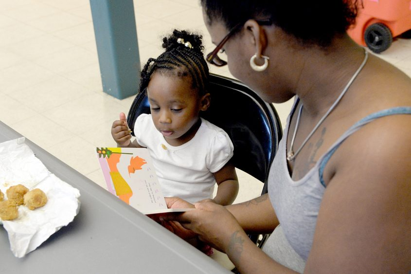 """Ciara Smith reads """"The Snowy Dog"""" to her daughter, Ari-Yonnah Smith, during a summer meals program in 2016."""
