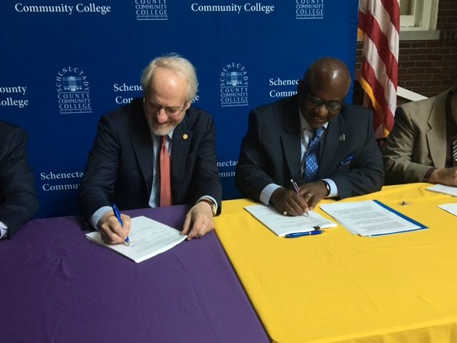 UAlbany interim President Jim Stellar (left) and SCCC President Steady Moono sign an agreement to ease student transfers.