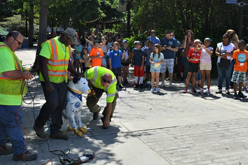 Workers install a Fiberglas Nipper in Albany as people look on.