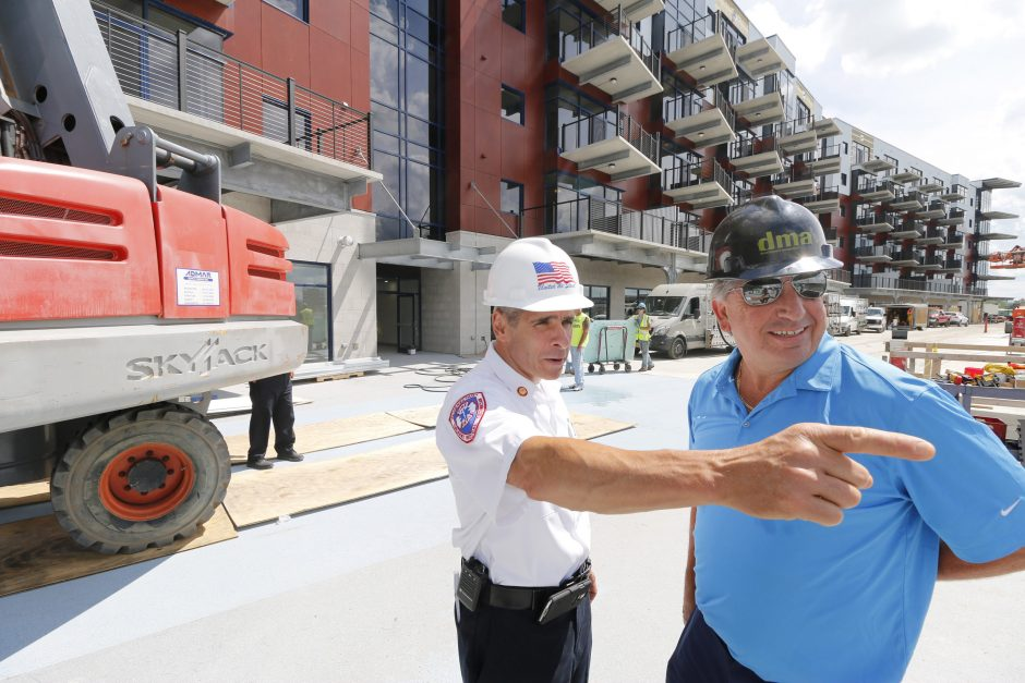 Schenectady Fire Chief Ray Senecal and Galesi Group CEO David Buicko chat outside the River House apartments on Friday.
