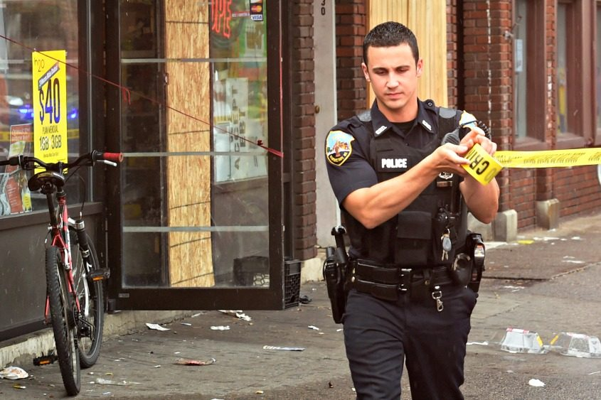 A Schenectady police officer stretches crime scene tape in front of Chubby's Pizza on Crane Street in August 2016.