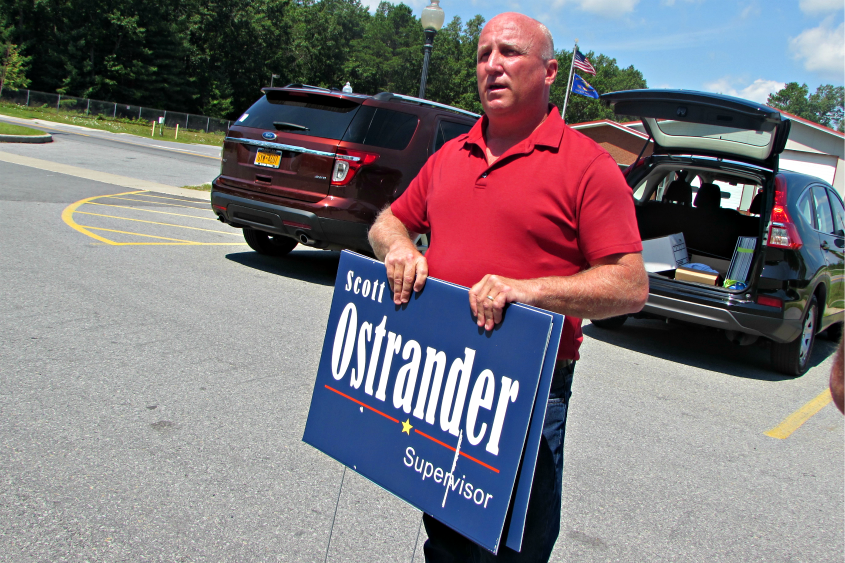 Scott Ostrander, a candidate for Milton town supervisor, displays one of his campaign signs after a news conference Wednesday.