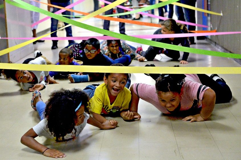Kids become secret agents — holding hands and crawling under lasers — at Martin Luther King Jr. Elementary School.