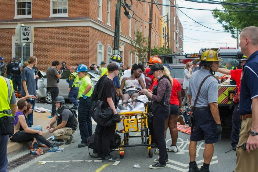 An injured woman is taken from the scene where a car plowed into people protesting a white nationalist rally in Charlottesville.