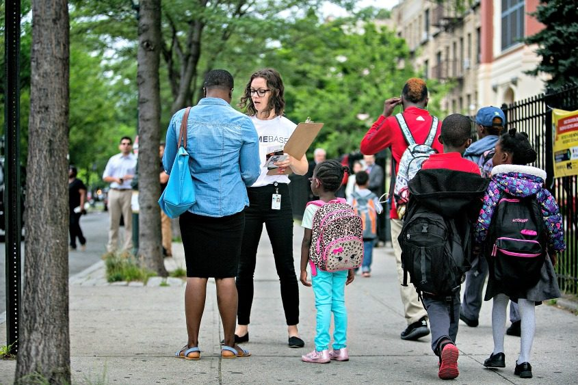 Amelia Watts of New York City's Human Resources Administration talks to parents outside of a school in Brooklyn.