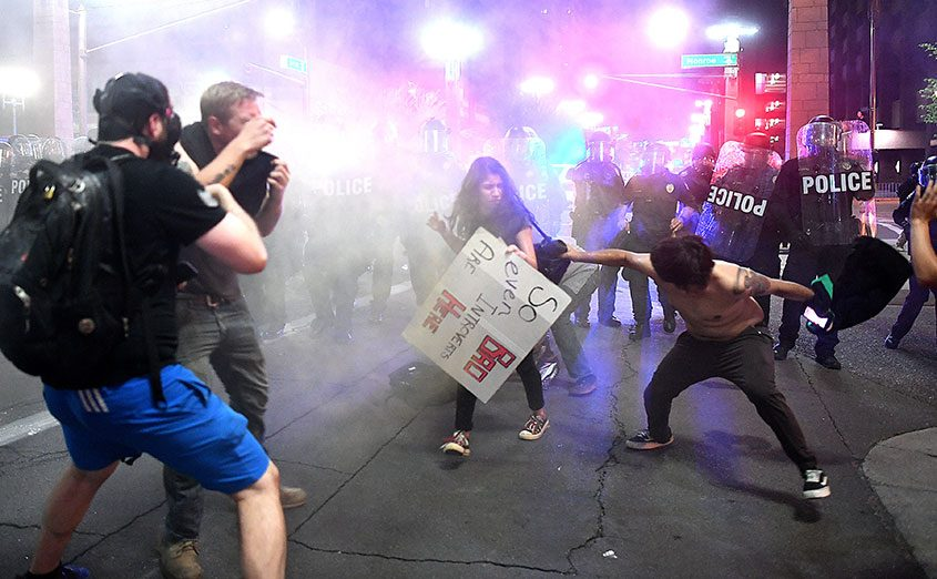 Police fire tear gas at protesters outside the convention center where President Donald Trump spoke in Phoenix.