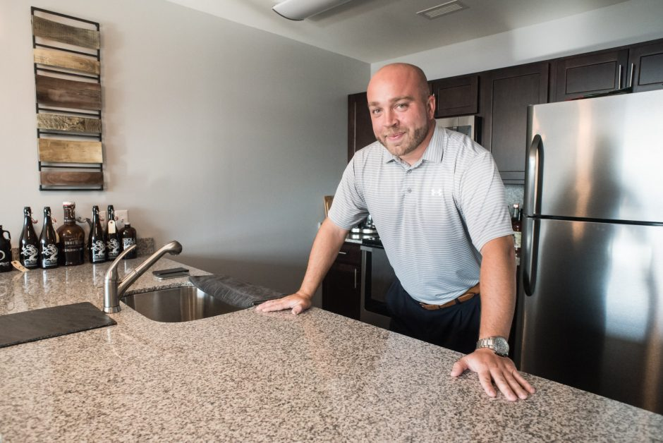 Justin Paquette poses for a photo in his River House apartment.