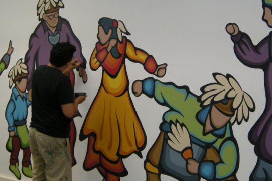 Native American artist Jay Havens works on a mural at the Iroquois Museum.