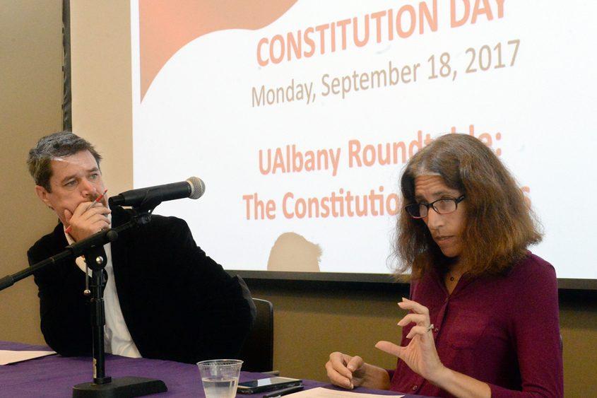 Julie Novkov, a University of Albany political science professor, talks while professor Matthew Ingram listens Monday.