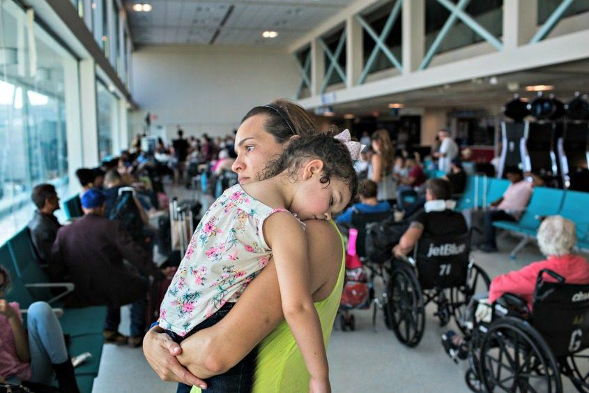 Jennifer Martinez of Dallas and her daughter Alanah Maldonado, 2, wait to board a flight at the airport in San Juan.