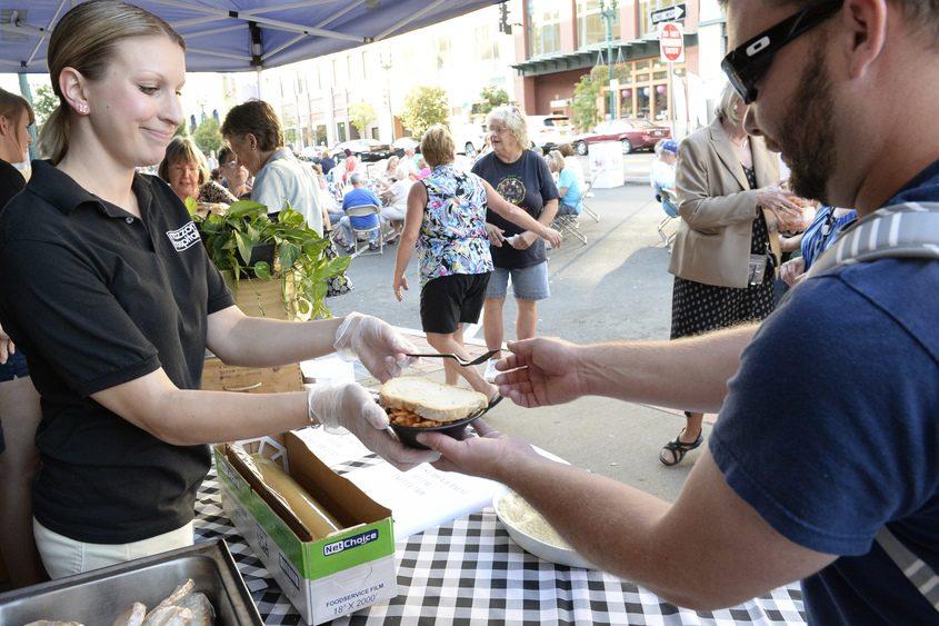 Mazzone Hospitality worker Heather Mlodzianowski serves food to Andy Lambhere on Wednesday.