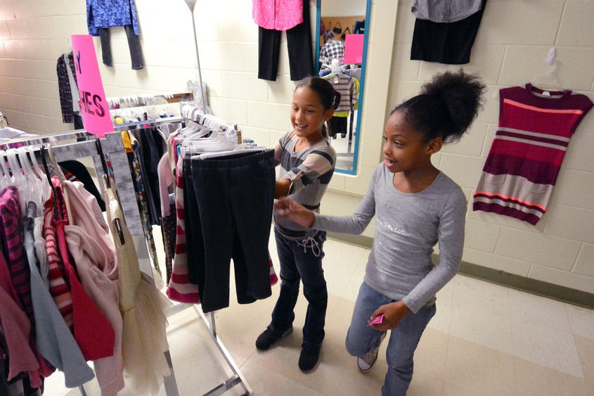 Third-graders Solymar Selim (left) and Jahida Sferrazza browse through racks of clothing in the shop.