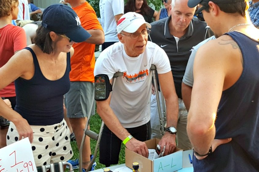 Pat Glover of Clifton Park helps with registration at the Shmaltz Brewery Beer Mile in September.