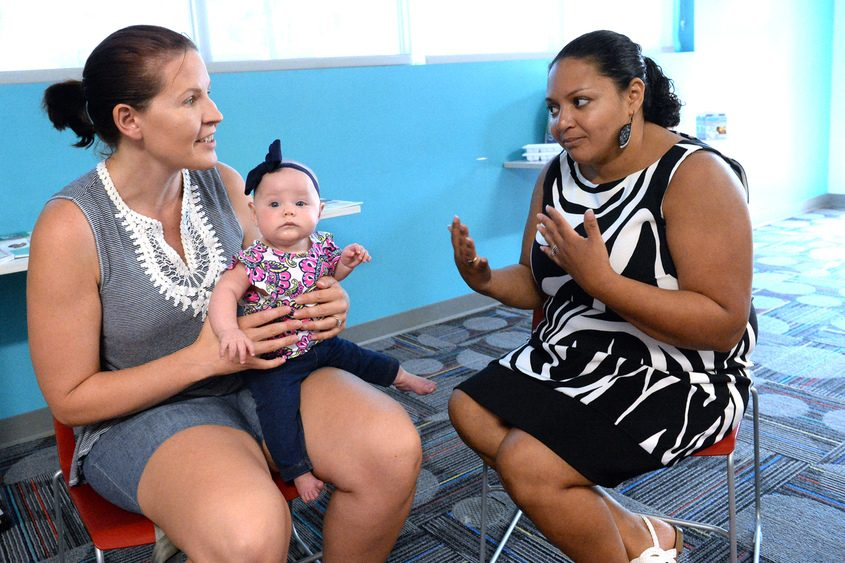 Lactation consultant Sarah Tice talks with Anne Cooper and 6-month-old daughter Maggie.