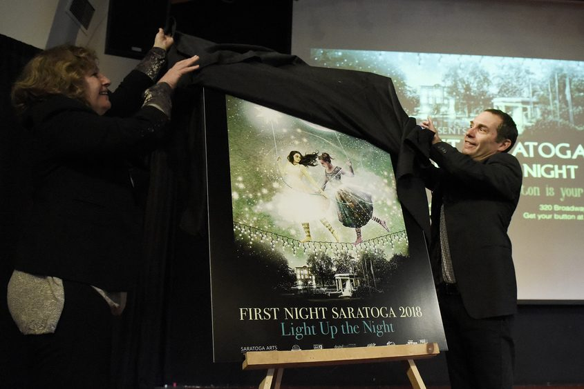 Saratoga Arts Director Joel Reed and artist Sharon Bolton unveil the First Night poster Tuesday during a news conference.