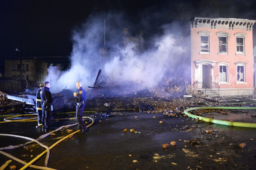 Cohoes police officers stand in front of the scene of a fire that leveled buildings on Remsen Street in Cohoes.