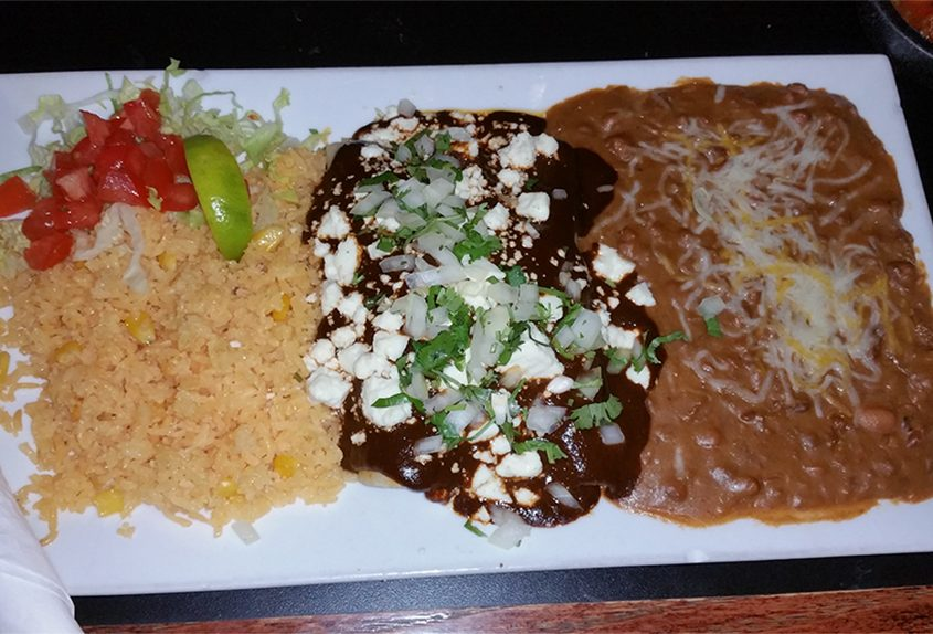 Chicken enchiladas with mole and Mexican rice and refried beans.