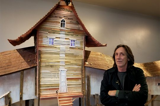 """""""Migration House"""" artist Robert Hite in front of his sculpture at Albany International Airport."""