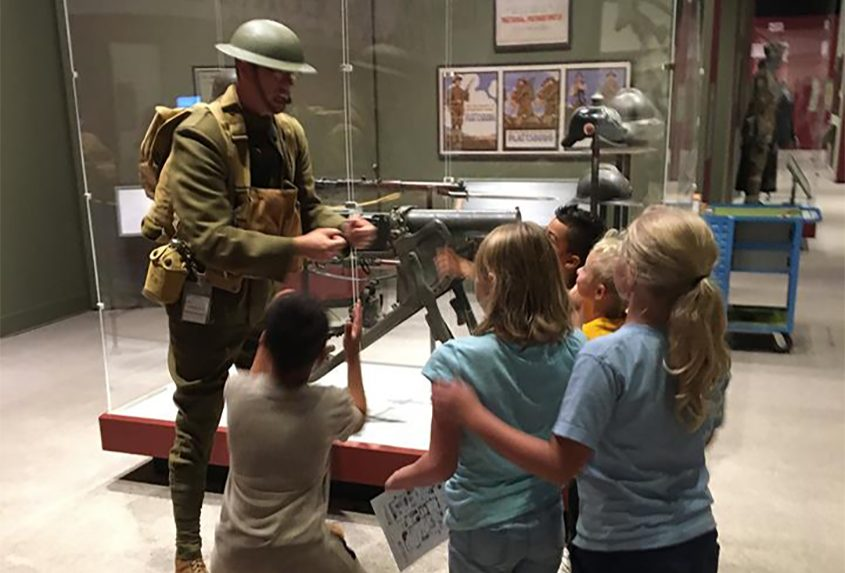 Museum educator James Jenkins shows young visitors to the state museum his World War I uniform.