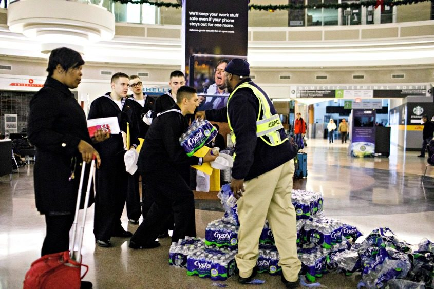Staff hands out bottled water to stranded travelers at the darkened Hartsfield-Jackson Atlanta International Airport on Dec. 17.