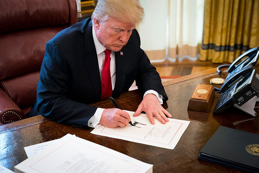 President Donald Trump signs a sweeping tax bill in the Oval Office of the White House, in Washington, Dec. 22, 2017.