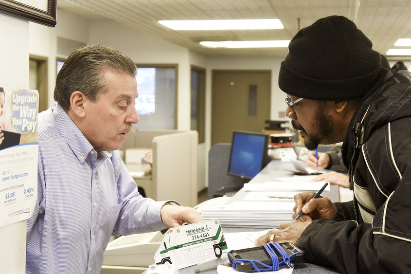 Glenville resident Al Jordan (right) fills out a check Wednesday to pay his taxes early.