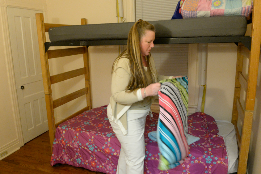 Danielle's House shelter director Lynette Clo makes a bed Tuesday in Amsterdam.