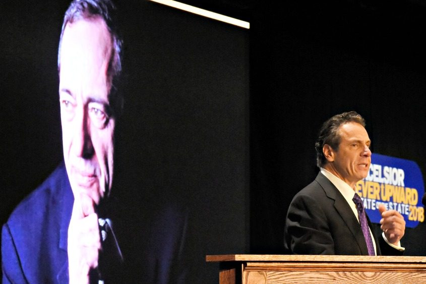 Gov. Andrew Cuomo delivers his address Wednesday in the shadow of a slide of his father, Mario.