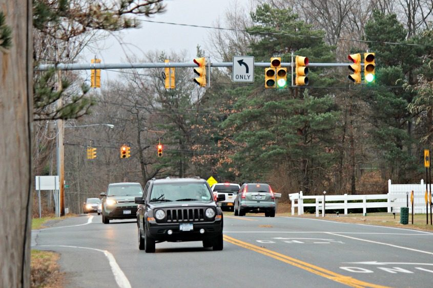 Cars go under the light at Sitterly Road and Crossing Boulevard. In the back is the Sitterly and Woodin roads light.