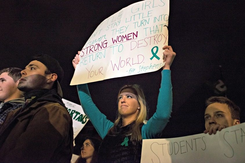 A woman holds a sign as students gather to listen to speakers during a protest Friday at Michigan State University.
