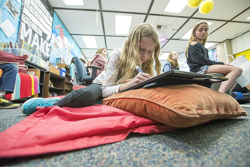 Amanda Garrett, 9, works on a project while lying on a mat at Anderson Elementary School in Newport Beach, Calif.