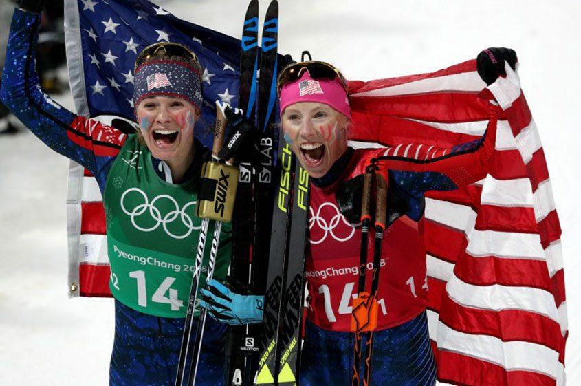 Jessica Diggins and Kikkan Randall celebrate winning their gold medal.