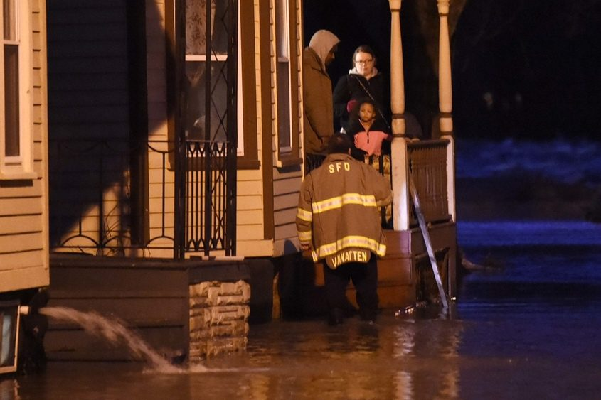 A Schenectady firefighter assists residents at 21 ingersoll Ave. after they were evacuated Wednesday.