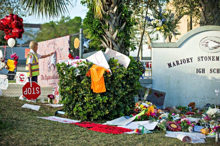Barbara Ramaley, a crossing guard at Marjory Stoneman Douglas High School, visits a memorial to those killed.