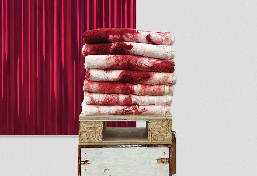 Seven towels splotched with red paint stacked on a box, by Rachel Howard, at MASS MoCA.