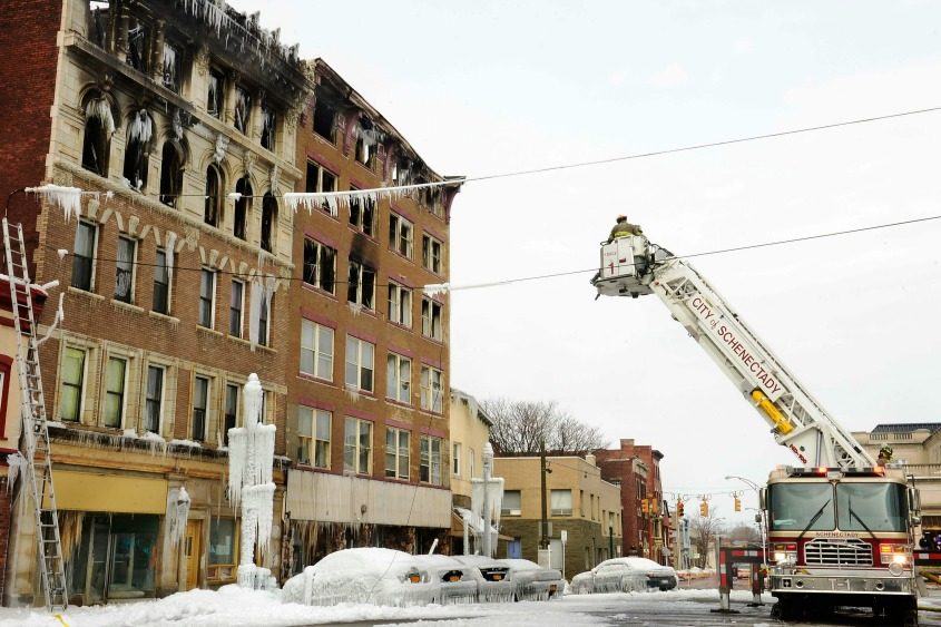 A Schenectady aerial platform truck pours water on ice-caked cars in front of 100-104 Jay St. in March 2015.
