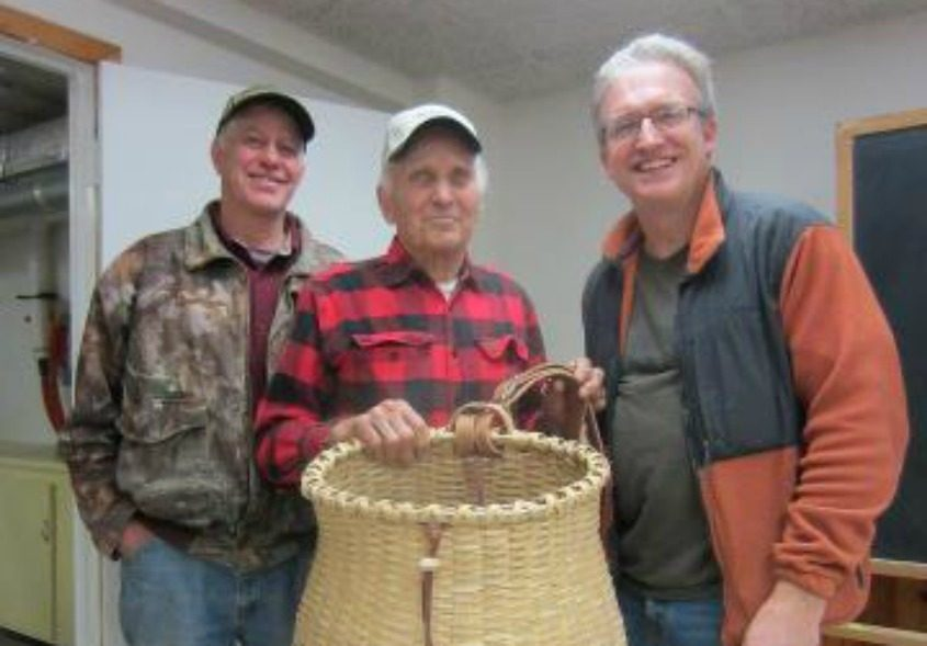 Jack Leadley Sr., center, holds one of his Adirondack pack baskets as his son, Rick Leadley, left, and Jim Schreiner look on.