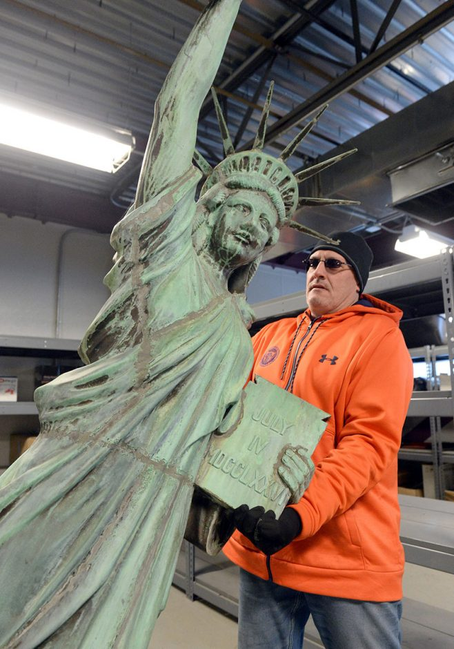 Schenectady Park Supervisor Jim Kochan moves the copper Statue of Liberty monument into place while in storage.