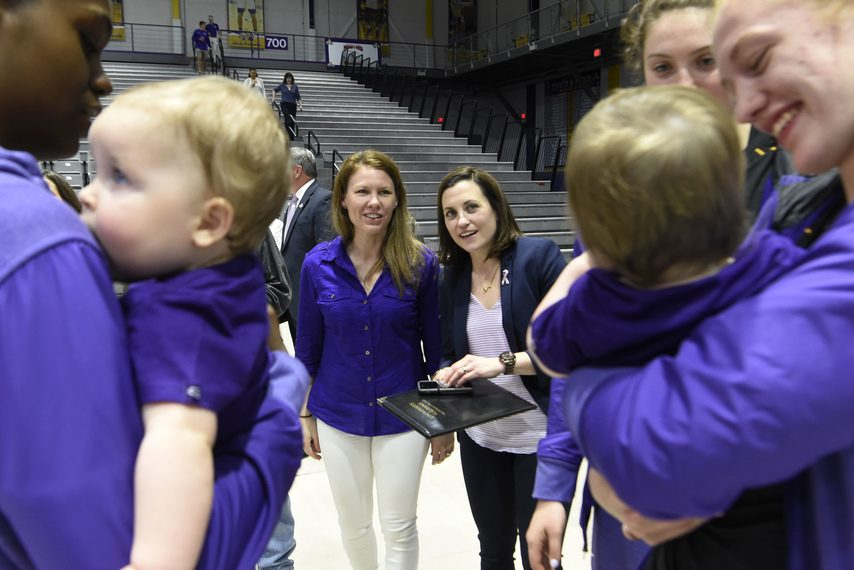 New University at Albany coach Colleen Mullen, right, and wife Lauren Mullen watch as players hold the couple's twin sons.