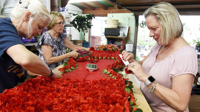 Florist Sue Garrett (right), and friends work on a floral blanket for the Belmont Stakes on Friday.