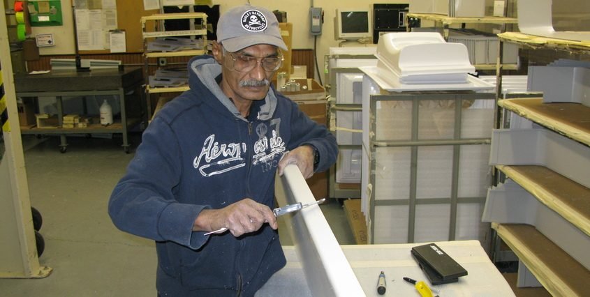 A Kintz Plastics employee deburrs the edge of a thermoformed plastic part at Kintz Plastics in Howes Cave in 2013.