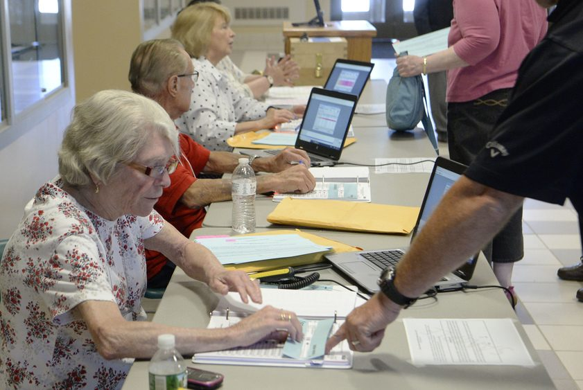 Marilyn Poitras shows voters how to cast their ballots for the school budget at Johnstown High School Tuesday.