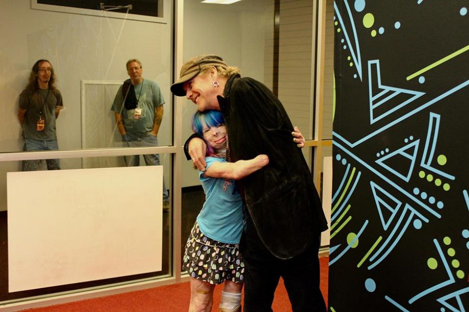 Safyre Terry embraces Def Leppard drummer Rick Allen during a visit last month in Albany