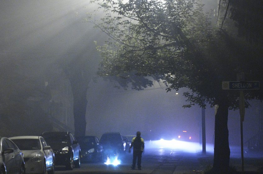 A Columbia Street resident lights a firework in the middle of the street on July 4, 2015.