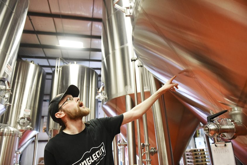 Eric Werner, a brewer with Singlecut Beersmiths, points at fermentation vessels.